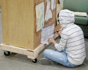 "Mackenzie Bacon works on a set piece for ""Leaving Iowa."" Photo by JANET SOWLE"