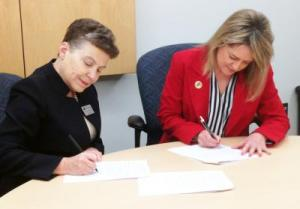 Dr. Christine Hammond, MMCC President, and Susan Wooden, BJSHS Superintendent, sign the State of Michigan application for Early College
